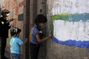 Children draw paintings on the wall of University of Sana'a reacting to the ongoing war in the country