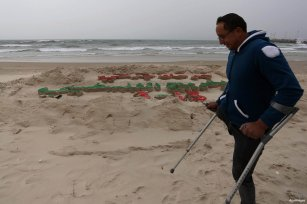 GAZA CITY, GAZA- A Palestinian artist Mohammed Totah with amputated leg poses for a picture behind a sand sculpture to mark Palestinian Wounded's Day