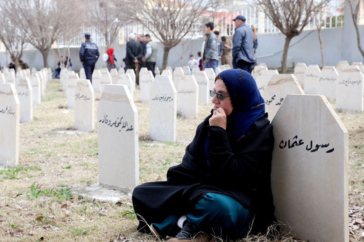 Iraqi-Kurds visit a grave site in Halabja near the monument for victims of the Halabja gas massacre that killed some 5,000 people [SHWAN MOHAMMED/AFP via Getty Images]