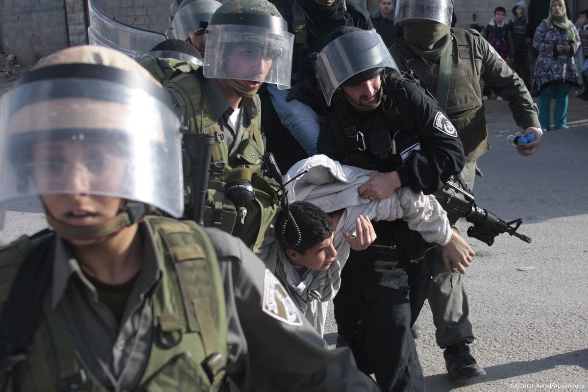 Image of Israeli forces violently arresting a Palestinian youth [Mohamar Awad/Apaimages]