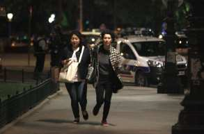 Two women run as police officers take security measures after a gunman killed a police officer at Champs Elysees in Paris, France on April 20, 2017 [Raphael Lafargue/Anadolu Agency]