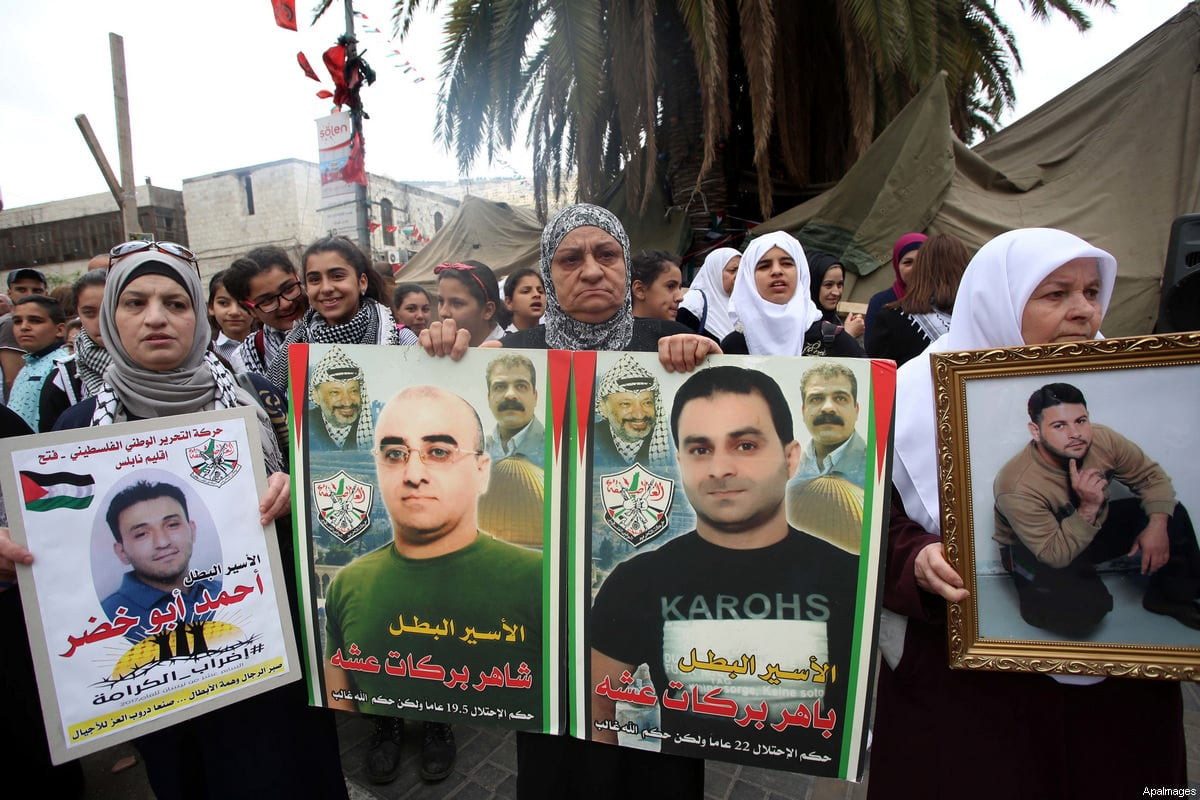 Palestinian protesters hold banners during a demonstration in solidarity with Palestinian prisoners on hunger strike in Israeli jails, in the West Bank of Nablus on April 23, 2017 [Ayman Ameen / ApaImages]