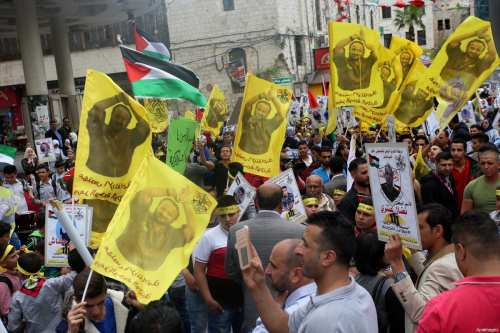 Palestinian protesters wave flags bearing the portrait of prominent prisoner and popular leader Marwan Barghouti during a demonstration in solidarity with Palestinian prisoners on hunger strike in Israeli jails, in the West Bank of Nablus on April 23, 2017 [Ayman Ameen / ApaImages]