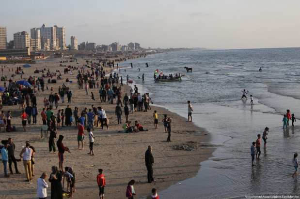 Children are seen playing on the beach to help cool off as the electricity crisis continues to worsen on 29 April in Gaza. [Image: Mohammad Asad / Middle East Monitor]