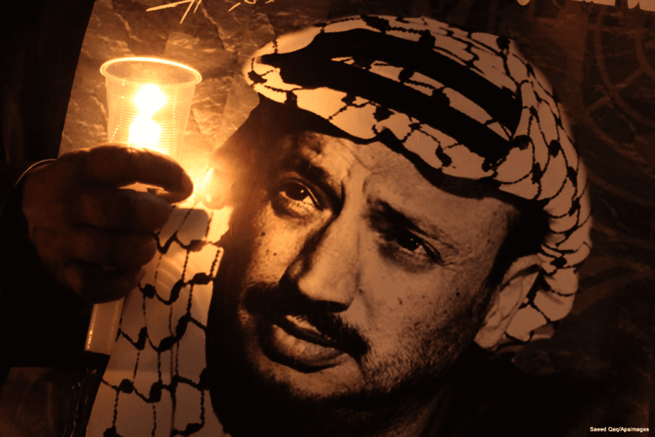 Palestinians hold posters and light candles as they commemorate the death of late Palestinian leader Yasser Arafat on 11 November 2013 [Saeed Qaq/Apaimages ]