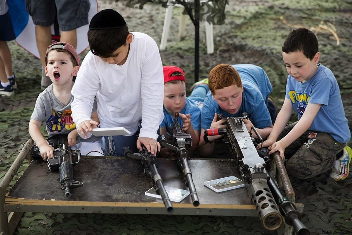 Israeli school children watch a military exercise where a Palestinian target is killed and then get the opportunity to handle some of the weapons on 9 May, 2017 [Shehab News Agency]