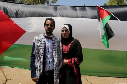 A Palestinian groom and his bride take part in their marriage ceremony at a sit-in in support of Palestinian hunger-striking prisoners in Gaza on 11 May, 2017 [Ashraf Amra/Apaimages]