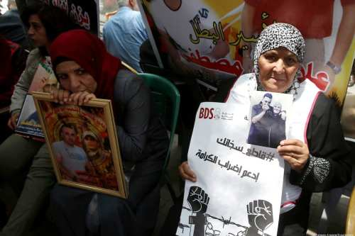 Palestinians hold placards during a sit-in in support of Palestinian hunger-striking prisoners held in Israeli jails, on 21 May, 2017, in the West Bank city of Nablus [Ayman Ameen/Apaimages]