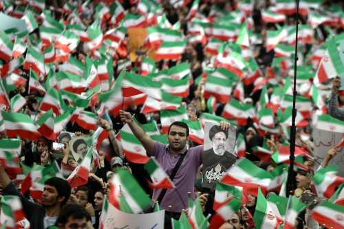 Supporters of Iranian cleric and presidential candidate Ebrahim Raisi wave flags during a rally prior to presidential elections in Tehran, Iran on May 16, 2017 [Fatemeh Bahrami/Anadolu Agency]