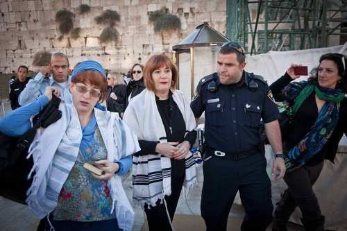 Image of Lesley Sachs and Rachel Cohen Yeshurun, activists of the group 'Women of the Wall', being detained by police officer for wearing Tallit (prayer scarf) in the vicinity of the Western Wall [Women of the Wall / Wikipedia]