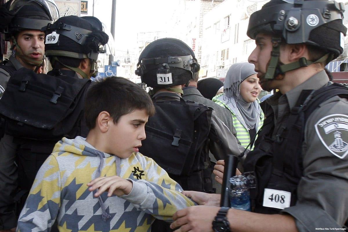 Image of Israeli forces arresting a Palestinian child on 22 November 2012 [Mahfouz Abu Turk/Apaimages]
