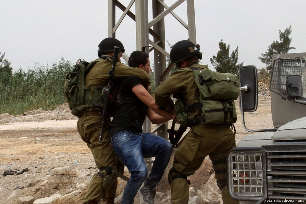 Image of Israeli soldiers arresting a Palestinian youth in West Bank on 31 May 2014 [Nedal Eshtayah/Apaimages]