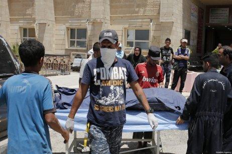 A dead body, left in a street, is being placed inside of a body bag by Iraqi army members in Mosul, Iraq on June 12, 2017 [Yunus Keleş / Anadolu Agency]