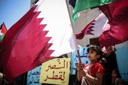 Palestinians hold Qatar and Palestine flags during a demonstration in support of Qatar, in Khan Yunis, Gaza on 14 June 2017 [Ali Jadallah/Anadolu Agency]