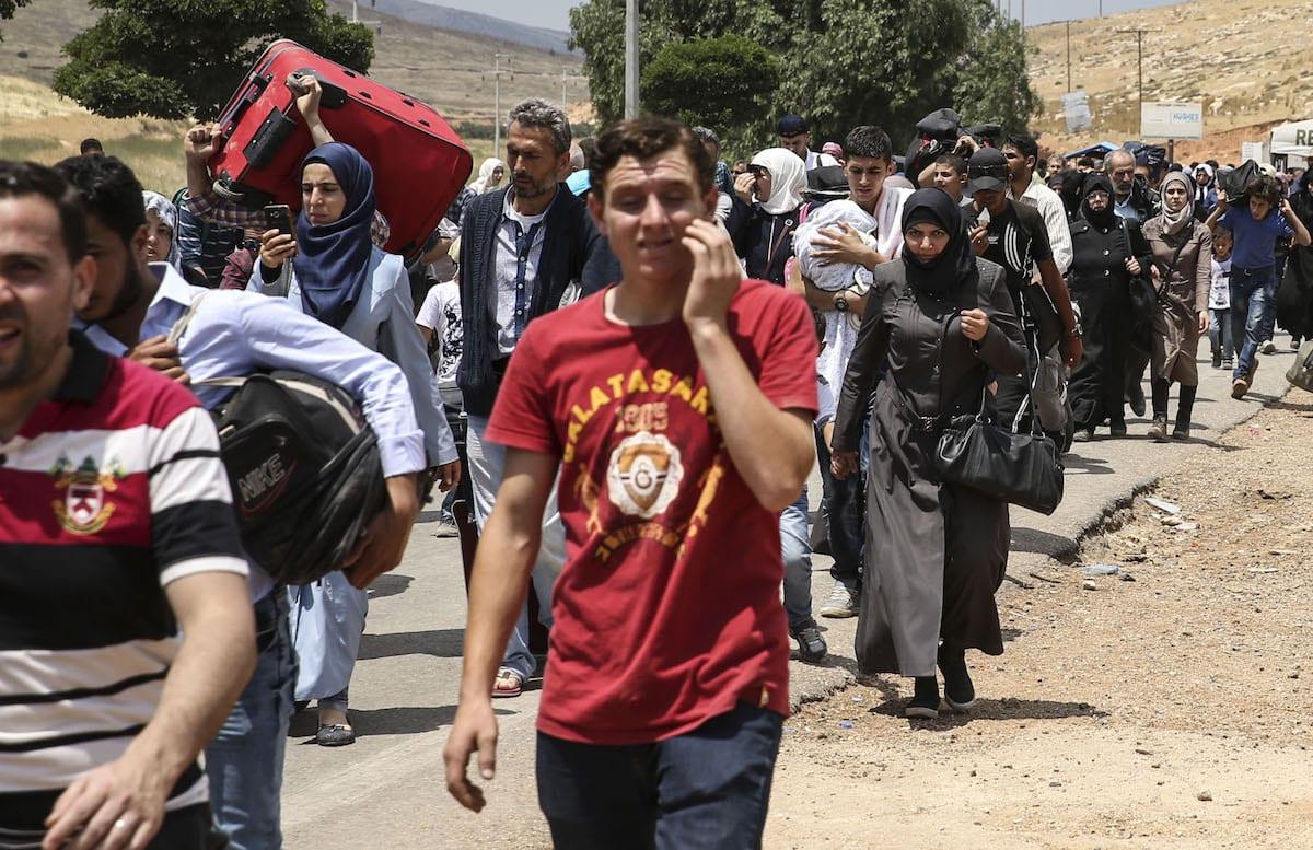 Syrians pass through Cilvegozu border gate to reach their hometowns before Eid Al-Fitr in Reyhanli, Hatay on 21 June 2017 [Cem Genco/Anadolu Agency]