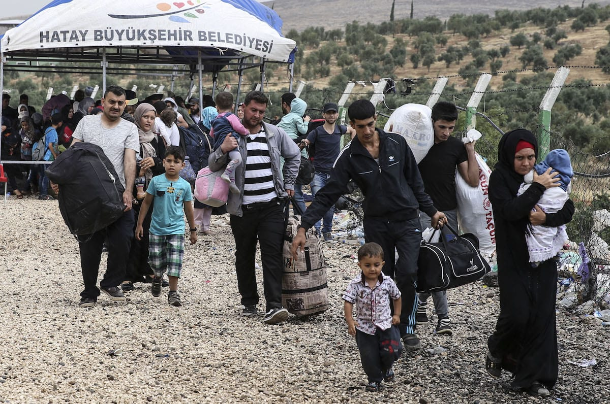 Syrians pass through Cilvegozu border gate to reach their hometown before Eid Al-Fitr in Reyhanli, Hatay on 21 June 2017 [Cem Genco/Anadolu Agency]