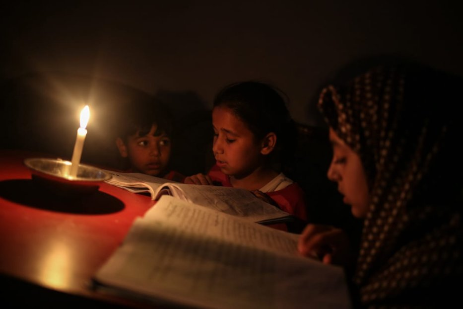 Palestinian kids read book by candle light due to power cut at the Jabalia Camp in Gaza City, Gaza on 27 June, 2017 [Ali Jadallah/Anadolu Agency]