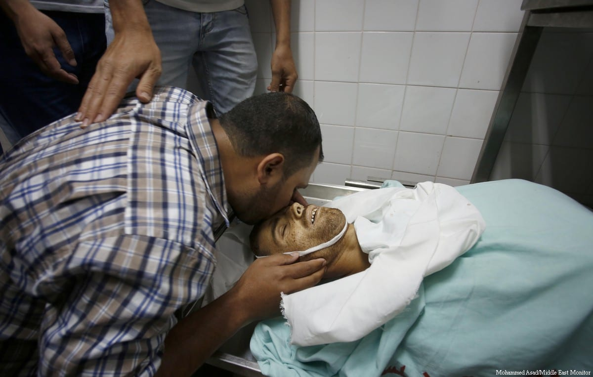 Father of 25-year-old Fadi Al-Najjar, who was killed by Israeli forces, kisses his son before his body is laid to rest in the Gaza Strip, on 6 June, 2017 [Mohammed Asad/Middle East Monitor]