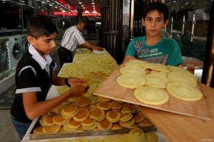 "GAZA CITY, GAZA- Palestinian children help to sell traditional pancakes known as ''Atayef""' at a market in Gaza city"