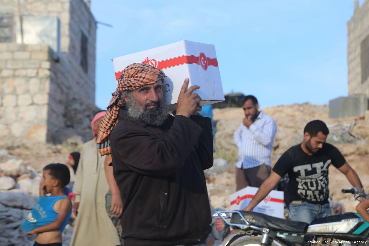 A Syrian man carries humanitarian aid, in Idlib, Syria on 23 June 2017 [İsmihan Özgüven/Anadolu Agency]