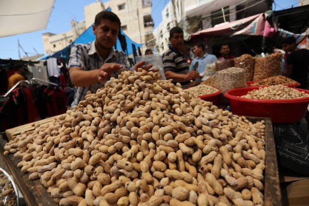 A Palestinian vendor sells nuts at a market ahead of Eid al-Fitr holiday, in Gaza city on June 24, 2017. Eid al-Fitr marks the end of Muslim's holy fasting month of Ramadan when faithfuls abstain from eating, drinking, smoking and sexual activities from dawn to dusk. Photo by Ashraf Amra