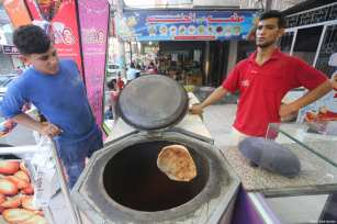Gaza bakers bake Afghan tamees bread, in Gaza June 17, 2017 [Mohammed Asad / Middle East Monitor]
