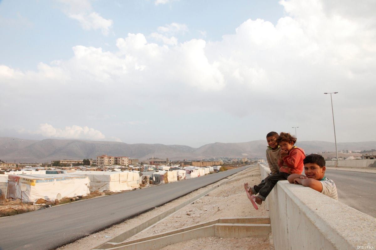 Syrian refugee children sit on a wall overlooking an 'informal tented settlement' in Lebanon's Bekaa valley on 5 November, 2013 [Russell Watkins/Flickr]