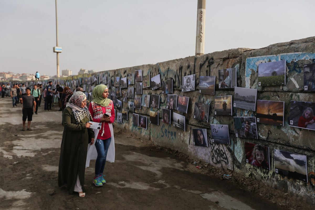 "Visitors view paintings during an open air exhibition called "" A Thousand Pictures From Besieged City"" in Gaza on July 12, 2017 [Mustafa Hassona/Anadolu Agency]"