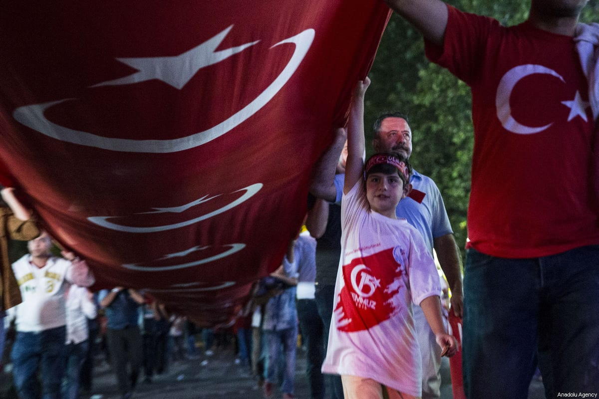 """People carry a 3 kilometers long Turkish flag within a march called """"National Unity March"""" which started from the area in front of historical 1st Turkish Grand National Assembly Building during July 15 Democracy and National Unity Day's events to mark July 15 defeated coup's 1st anniversary in Ankara, Turkey on July 15, 2017 [Metin Aktas / Anadolu Agency]"""
