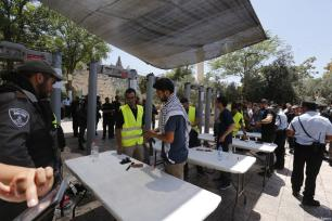 Israeli security forces check Palestinians and their belongings with metal dedectors after Al Aqsa Mosque re-opened for prayers near the Lion's Gate, in Al Aqsa Mosque in Jerusalem on July 16, 2017 [Alkharouf Mostafa / Anadolu Agency]