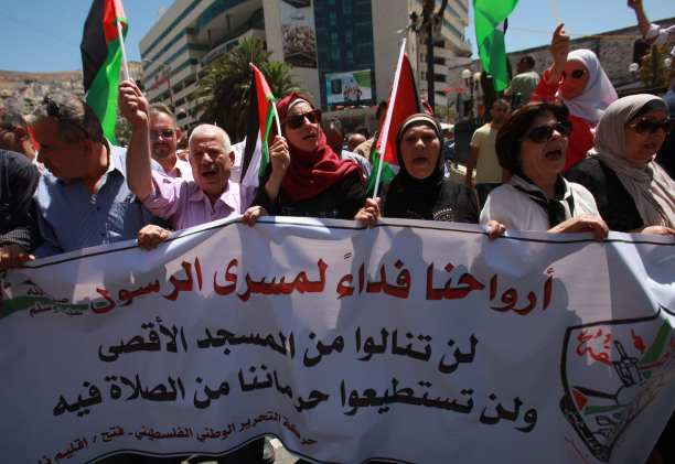 Palestinians hold banners and shout slogans during a protest against Israeli violations towards the al-Aqsa Mosque on 16 July 2017 [Nedal Eshtayah/Anadolu Agency]