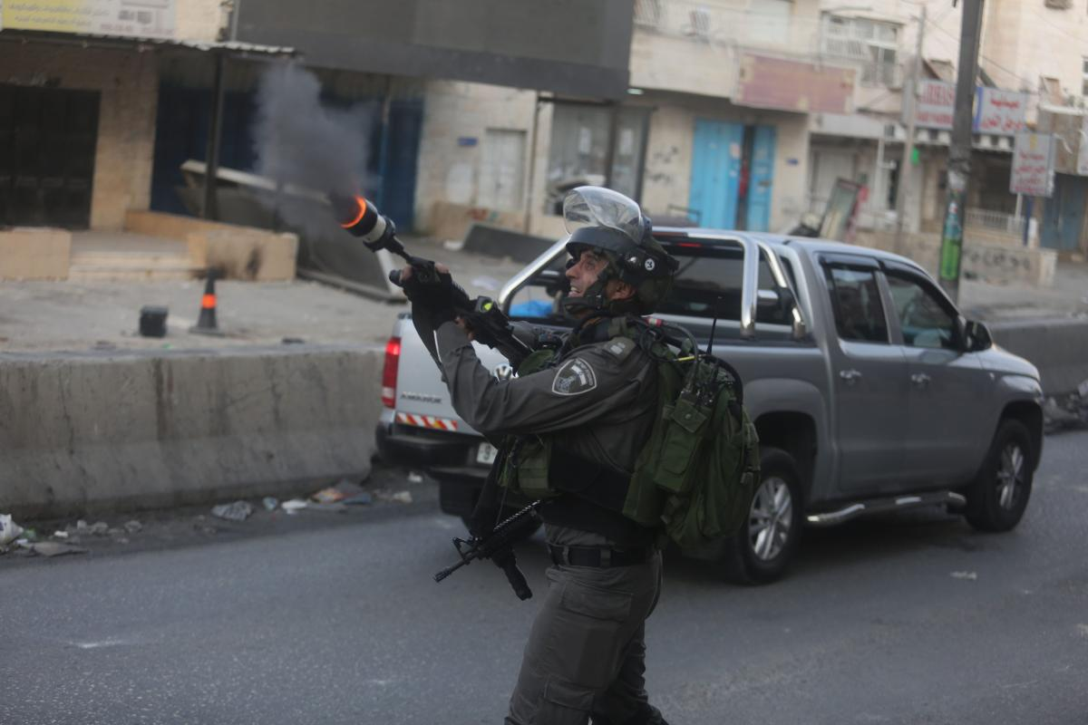 Israeli security forces intervene to Palestinian protesters using teargas bomb during clashes in Ramallah, West Bank, on 23 July, 2017 [Issam Rimawi/Anadolu Agency]