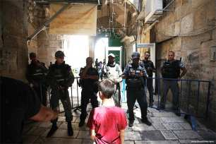 A Palestinian boy stands in front of Israeli soldiers who have blocked the entrance to Al-Mosque on 18 July 2017 [Mostafa Alkharouf/Anadolu Agency]