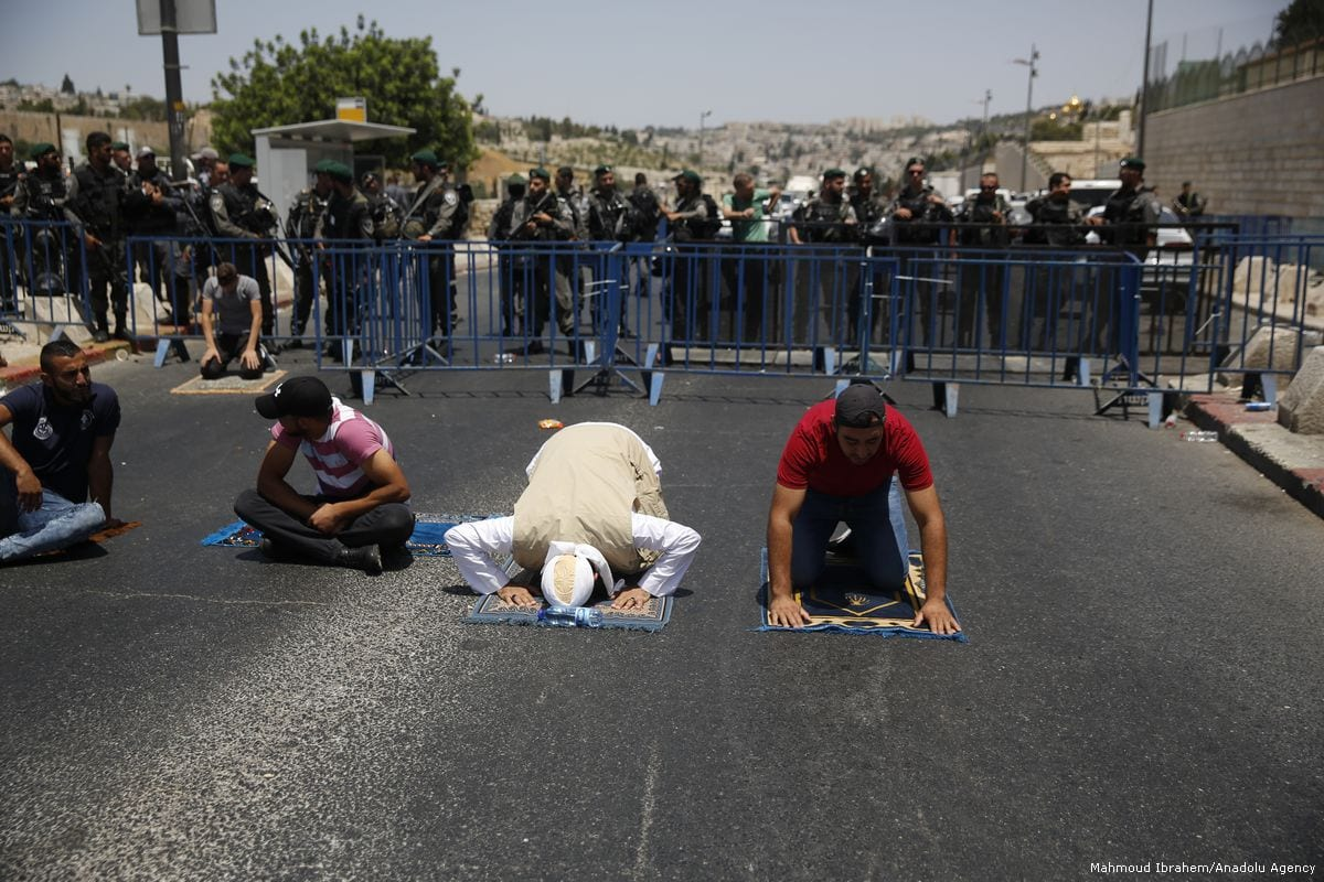 Palestinian Muslims gather to perform Friday Prayer at one of the entrances of Al Aqsa Mosque Compound in Jerusalem, on 28 July 2017 [Mahmoud Ibrahem/Anadolu Agency]
