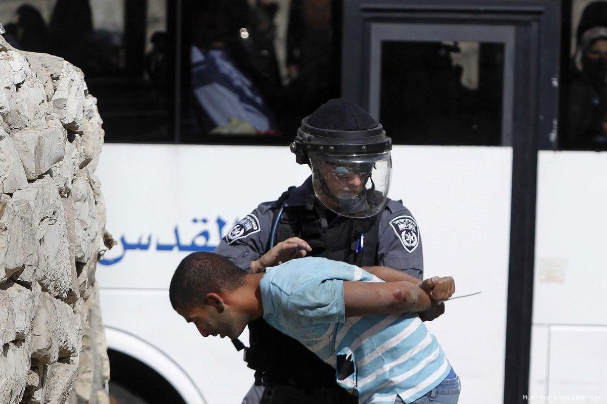 An Israeli border police arrests a Palestinian man, seen on October 15, 2014 [Muammar Awad/Apaimages]