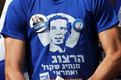 A supporter of the centre-left Zionist Union wears a T-shirt showing Isaac Herzog, one of the party's leaders, outside a polling station in Tel Aviv in 2015 [Baz Ratner/Reuters]