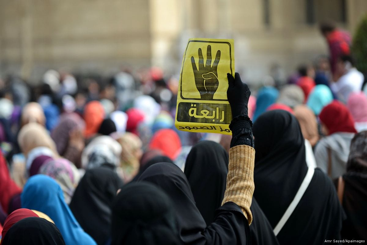 An Egyptian student holds the Rabaa sign during a protest against the military rule on 18 February 2015 [Amr Sayed/Apaimgaes]