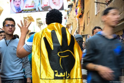 Egyptian supporters of the Muslim Brotherhood and ousted President Mohamed Morsi, flash the Rabaa sign during a demonstration against the military in Cairo on 24 April 2015 ]Amr Sayed/Apimages]