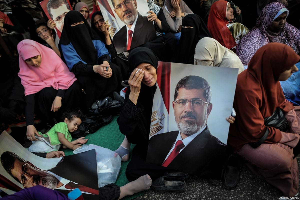 A file photo dated July 4, 2013 shows a female supporter of Mohammed Morsi gesturing as she holds a portrait of him in Rabia Adaweya Square a day after the military coup in Cairo, Egypt. ( Mohammed Elshamy - Anadolu Agency )