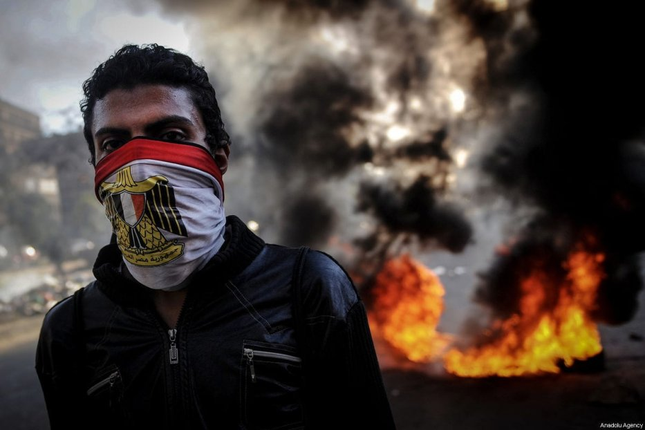 A file photo dated December 6, 2013 shows a supporter of ousted Mohammed Morsi wearing an Egyptian flag to conceal their identity during clashes between pro-Morsi supporters and police forces in the streets of El Zeitun district near the Qubba Presidential Palace in Cairo, Egypt. ( Mohammed Elshamy - Anadolu Agency )
