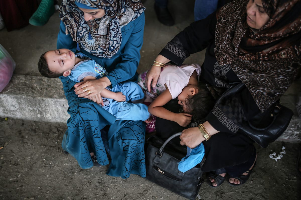 Two women hold their kids as they wait to cross the Rafah Border with their luggage, in Rafah, Gaza on August 16, 2017. ( Mustafa Hassona - Anadolu Agency )