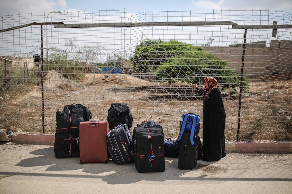 A woman stands next to her luggage as she waits to cross the Rafah Border in Rafah, Gaza on August 16, 2017.( Mustafa Hassona - Anadolu Agency )