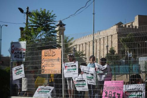 Palestinians hold banners during a protest against Israeli restrictions on the Ibrahimi Mosque in Hebron, occupied West Bank on 28 August 2017 [Mamoun Wazwaz/Anadolu Agency]