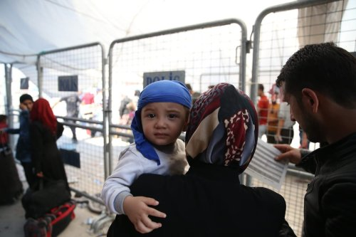 A baby is seen in his mother arms as Syrian refugees pass through Oncupinar border gate to reach their hometowns before Eid al-Adha in Kilis, Turkey on 29 August, 2017 [Ensar Özdemir/Anadolu Agency]