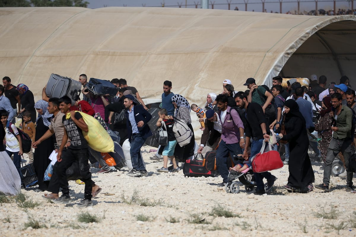 Syrian refugees with their belongings pass through Oncupinar border gate to reach their hometowns before Eid al-Adha in Kilis, Turkey on 29 August 2017 [Ensar Özdemir/Anadolu Agency]