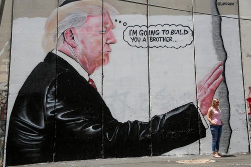 A tourist stand in front of a graffiti depicting US President Donald Trump on the controversial Israeli separation barrier in the West Bank town of Bethlehem on 8 August, 2017 [Shadi Hatem/Apaimages]