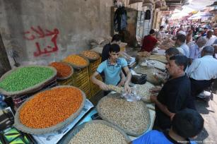 Palestinians shop at the market in preparation for Eid. Sellers and vendors have seen a decrease in customers due to the austerity Palestinians are facing due to PA's policies. [Mohammed Asad/Middle East Monitor]