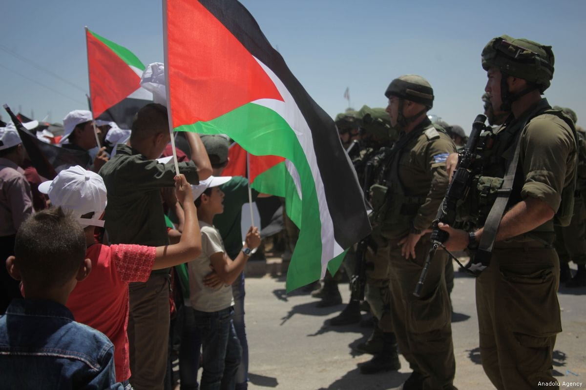 Raising the flag: Palestinians demonstrate in occupied Hebron against illegal Israeli settlements in the occupied West Bank on 4 August 2017 [Mamoun Wazwaz/Anadolu Agency]
