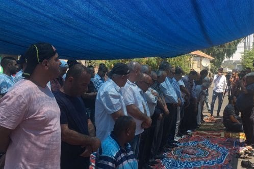 Friday prayers area held on 11 August 2017 outside the Shamasna home in the Sheikh Jarrah neighbourhood of occupied East Jerusalem to show solidarity as the family is facing imminent evacuation to make room for Israeli settlers who claim they own the property. [Twitter/Quds TV]