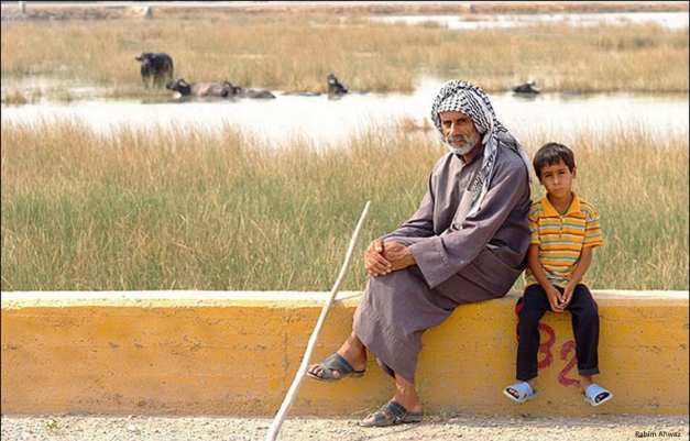 Image of Ahwazi Arabs sitting in front of a polluted river [Rahim Ahwaz]